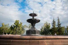 Large granite fountain in a city park on a background of a bright blue sky Royalty Free Stock Photo