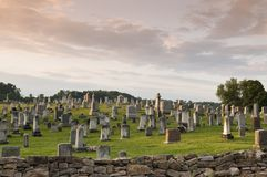 Large Graveyard in the Country. Rural graveyard filled with old grave stones set on picturesque hill behind fieldstone wall Royalty Free Stock Photos