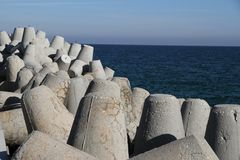 Large gray breakwaters installed at the seaport to reduce the waves. Royalty Free Stock Images