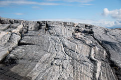 Large gray rock on the sky background. Close up Stock Image
