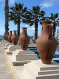 Large Grecian urns by palm trees. Line of urns by blue sky and palm trees Royalty Free Stock Photography
