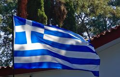 Large Greek flag flapping. In a park in front of church roof with tiles stock images