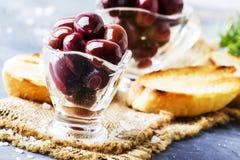 Large greek kalamata olives, gray background, selective focus. Food still life royalty free stock photo