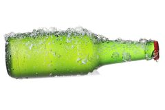 Large green beer bottle and icy snow Stock Photography