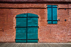 Large green metal doors in old brick building Stock Photography