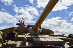A large green military metal armored deadly dangerous iron Russian Syrian battle tank with a gun turret and a goose. Is parked parked against a blue sky and stock image