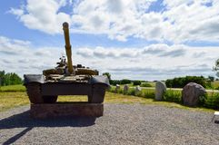 A large green military metal armored deadly dangerous iron Russian Syrian battle tank with a gun turret and a goose. Is parked parked against a blue sky and royalty free stock images