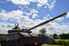 A large green military metal armored deadly dangerous iron Russian Syrian battle tank with a gun turret and a goose. Is parked parked against a blue sky and royalty free stock image