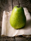 Large green pear, one stands on a linen cloth, on a wooden table. Royalty Free Stock Images