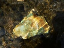 Large green stone fluorite in water. Large green stone fluorite in a dark clear water Royalty Free Stock Photography