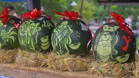 Big Watermelons Decorated with Carved Inscriptions on Market. Large green watermelons with red ribbons and carved inscriptions symbolizing happiness stand on hay