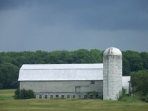 Large grey barn and silo in a field in Vermont. A large grey barn with a tall silo stand alone in a field in Vermont under a dark threatening sky Stock Photos