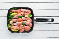 Large grilled shrimp in a frying pan. Tiger prawns. Top view. Free space for your text. On the old background stock images