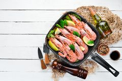 Large grilled shrimp in a frying pan. Tiger prawns. Top view. Free space for your text. On the old background royalty free stock photos