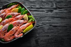 Large grilled shrimp in a frying pan. Tiger prawns. Top view. Free space for your text. On the old background royalty free stock photo