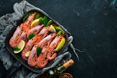 Large grilled shrimp in a frying pan. Tiger prawns. Top view. Free space for your text. On the old background royalty free stock photography