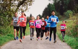 Large group of multi generation people running a race competition in nature. stock image