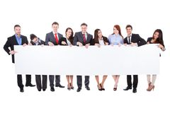 Large group of businesspeople presenting banner Stock Photos