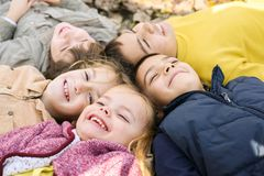 Large group of children. Happy children lying on falling leaves. Close up royalty free stock image