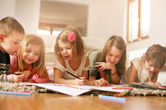 Large group of children lying on the floor. Large group of children write their homework at home Royalty Free Stock Photos
