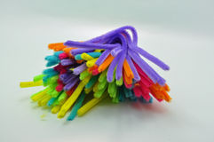 A large group of coloured pipe cleaners. A group of pipe cleaners against a light blue background royalty free stock photos