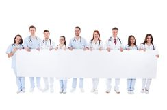 Large group of doctors and nurses with a banner. Large group of doctors and nurses holding a long blank white banner with copyspace for your text isolated on Royalty Free Stock Images