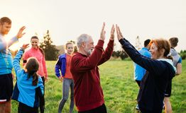 Large group of fit and active people resting after doing exercise in nature. royalty free stock photo