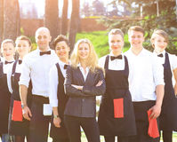 A large group of friendly waiters and waitresses standing in a row behind each other Royalty Free Stock Photos