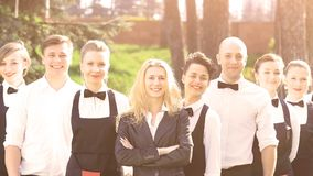 A large group of friendly waiters and waitresses standing in a row behind each other. A large group of friendly waiters and waitresses standing row behind each Royalty Free Stock Photos