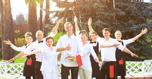 A large group of happy and emotional waiters standing in a row behind each other Stock Image