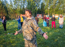 Large group of happy peoples play roundelay. Cosmos Village, Almaty Province, Kazakhstan - 16 August 2015: Large group of happy peoples play roundelay and stand Stock Images
