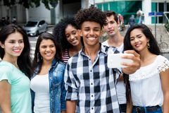 Large group of international young adults taking selfie with phone outdoor in the summer royalty free stock images