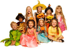 Large group of kids in costumes isolated on white. Group of kids, boys and girls sitting together in Halloween costumes with carved pumpkin isolated on white Royalty Free Stock Photo