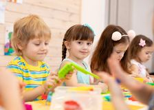 Large group of kids play with modeling clay stock photos