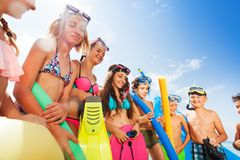 Large group of kids ready to swim in sea. Large group of kids standing in a row with swimming equipment ready to swim in sea stock image