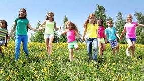 Large group of kids run in dandelion field. Holding hands at sunny spring day stock video