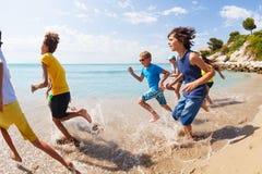 Group of kids running run on beach water edge. Large group of kids running on the beach on the water edge on summer hot vacation day Stock Image
