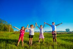Large group of kids running in summer field with sky background stock photography