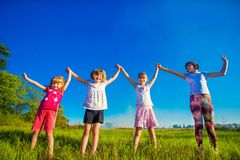 Large group of kids running in summer field with sky background royalty free stock photo