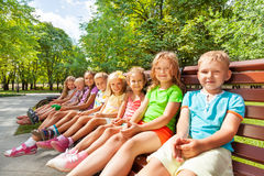 Large group of kids sitting on the bench Royalty Free Stock Photography
