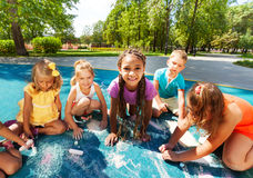 Large group of little kids draw with chalk. Big group of boys and girls drawing with chalk on playground in the park on sunny summer day Stock Images