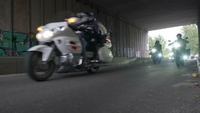 Large group of motorcyclists driving under a bridge with working headlights. Stock footage stock video