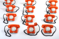 Large group of orange telephones. Especial phone looks forward to hearing. Close up large group of orange telephones Royalty Free Stock Photography