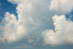 A large group of paragliders flies in the sky against the background of clouds. Competitions paragliders on the ridge Borzhava in the Carpathians in Ukraine Royalty Free Stock Photo