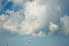 A large group of paragliders flies in the sky against the background of clouds. Competitions paragliders on the ridge Borzhava in the Carpathians in Ukraine Royalty Free Stock Photography