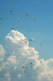 A large group of paragliders flies in the sky against the background of clouds. Competitions paragliders on the ridge Borzhava in the Carpathians in Ukraine Stock Image