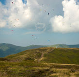 A large group of paragliders fly in the sky above the mountains. Competitions paragliders on the ridge Borzhava in the Carpathians in Ukraine Stock Photo