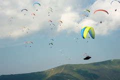 A large group of paragliders fly in the sky above the mountains. Competitions paragliders on the ridge Borzhava in the Carpathians in Ukraine Royalty Free Stock Images