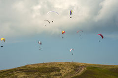 A large group of paragliders fly in the sky above the mountains. Competitions paragliders on the ridge Borzhava in the Carpathians in Ukraine Royalty Free Stock Photos