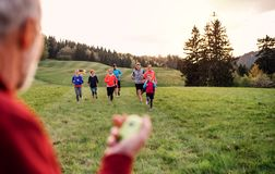 Large group of people cross country running in nature, checking time. stock image